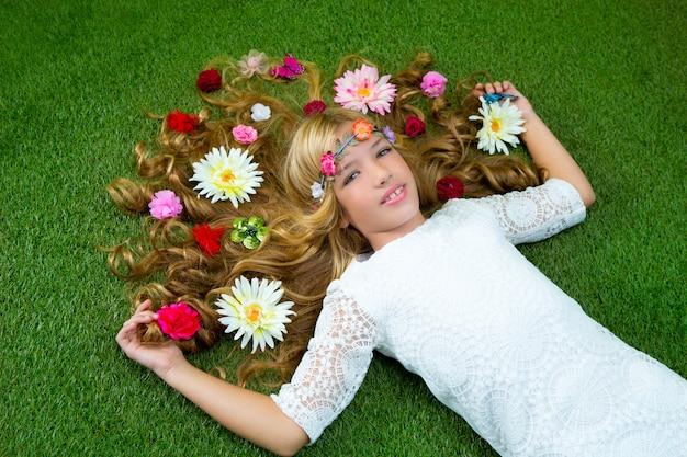 Garota loira primavera com flores no cabelo sobre grama