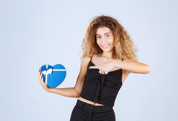 Garota loira segurando uma caixa de presente em forma de coração azul e apontando para ela.