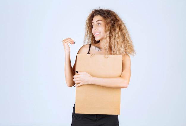 Garota loira segurando uma sacola de compras de papelão e apontando para outro lugar.
