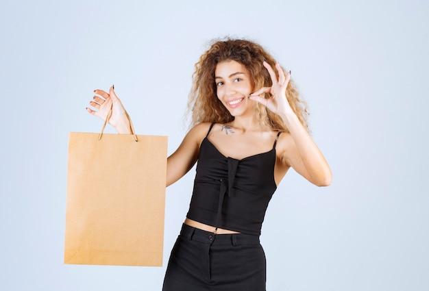 Garota loira segurando uma sacola de papelão e parece satisfeita.