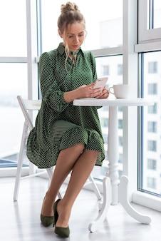Garota loira senta-se à mesa ao lado da janela, segurando um telefone celular e olhando para a tela