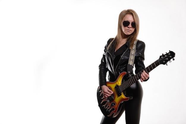 Garota loira sexy com óculos de sol, jaqueta de couro preta tocando guitarra elétrica preta