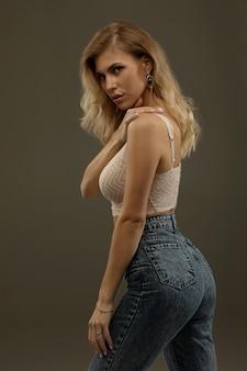 Garota loira sexy com os lábios carnudos, posando de jeans e roupas íntimas.