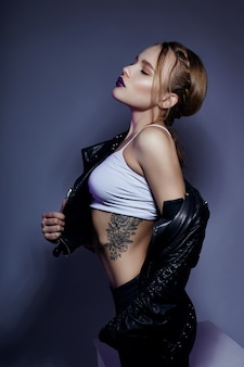 Garota loira sexy com tatuagem na jaqueta de couro