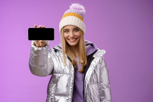 Garota loira simpática e confiante no chapéu de jaqueta brilhante prateada ao ar livre segurar o smartphone na horizontal, mostrando a exibição do telefone móvel, um sorriso assertivo, recomendo o uso do aplicativo, fundo roxo.