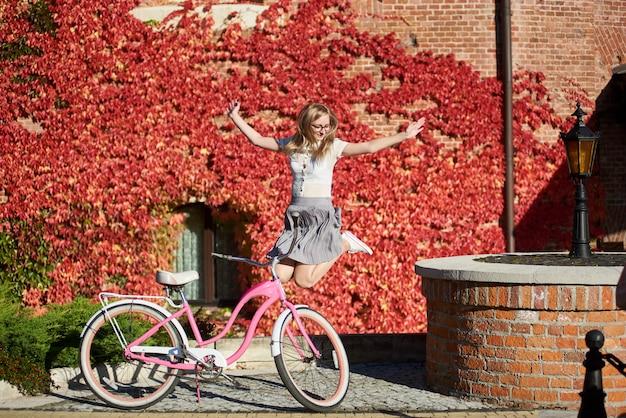 Garota loira sorridente atraente pulando voando no ar na bicicleta da senhora-de-rosa em dia ensolarado quente e brilhante no fundo da casa coberta de hera vermelha linda.