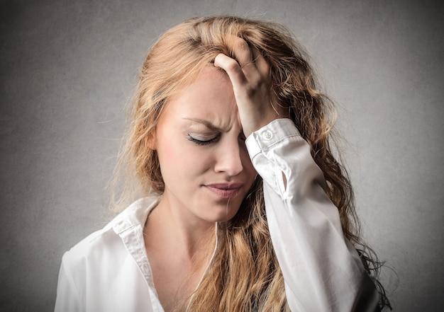 Garota loira tendo uma dor de cabeça