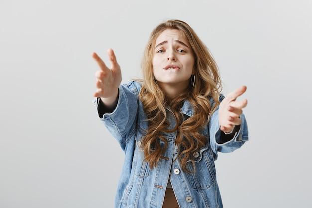 Garota loira tentadora estendendo as mãos com desejo, querendo segurar ou pegar algo
