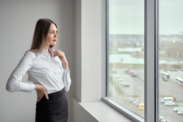 Garota magra com camisa branca e saia preta justa posando perto da janela