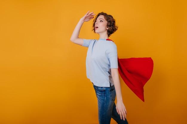 Garota magra de jeans e manto vermelho se divertindo