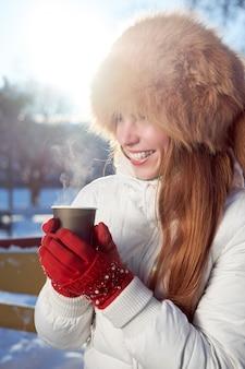 Garota magra ruiva, vestida com chapéu de pele de raposa e jaqueta branca, tomando café para ir no dia frio de inverno e rindo.