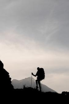 Garota magro silhueta em pé sobre a rocha com caminhadas mochila e bengalas