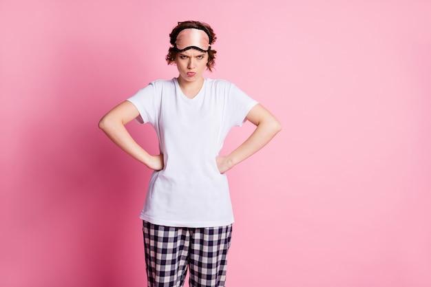 Garota mal-humorada colocando os braços nas laterais sobre um fundo rosa