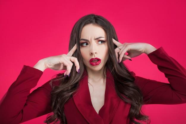 Garota maluca na parede rosa. jovem mulher bonita com maquiagem brilhante. a morena agarrou a cabeça dela.