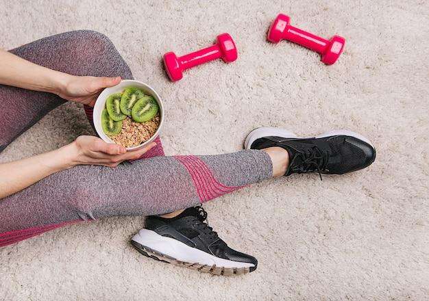 Garota mantém um prato com muesli e kiwi após treino de fitness com halteres
