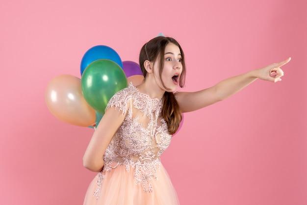 Garota maravilhada com boné de festa segurando balões apontando para algo