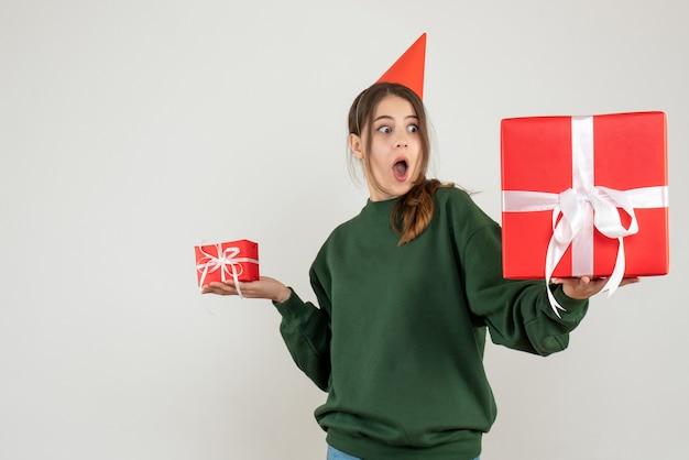 Garota maravilhada com chapéu de festa olhando para seu grande presente de natal