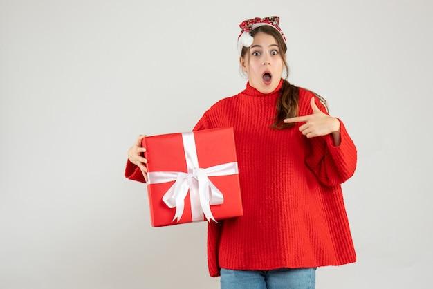 Garota maravilhada de frente com chapéu de papai noel apontando o dedo para o presente