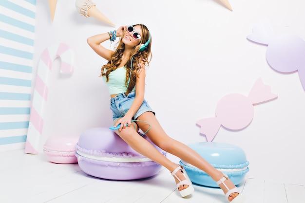 Garota maravilhosa com cabelo castanho claro brilhante, curtindo música durante o descanso na cadeira de biscoitos. retrato de uma jovem deslumbrante usando um acessório da moda e ouvindo a música favorita em fones de ouvido grandes.