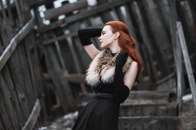 Garota marcante com longos cabelos vermelhos em roupas pretas. mulher de vestido preto e peles no pescoço, com luvas pretas longas posando na natureza de inverno.
