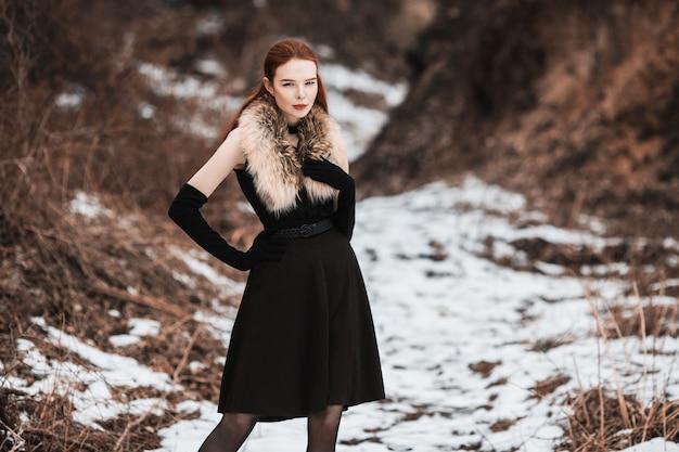 Garota marcante com longos cabelos vermelhos em roupas pretas. mulher de vestido preto e peles no pescoço, com luvas pretas longas, posando no fundo da natureza do inverno. estilo de rua feminino. modelo elegante bonito