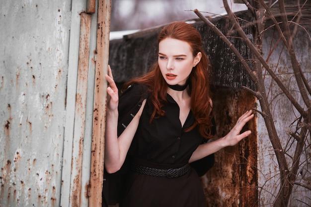 Garota marcante com longos cabelos vermelhos em roupas pretas. uma mulher em um vestido preto e jaqueta posando em um fundo de natureza inverno. estilo de moda de rua feminino. modelo elegante bonito