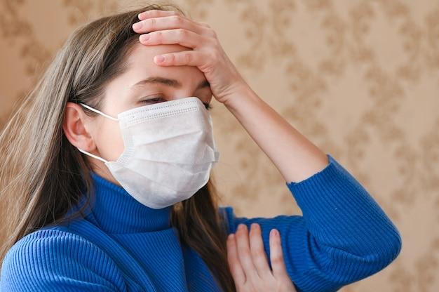 Garota mascarada com dor de cabeça. fechar-se. os primeiros sinais de coronavírus.