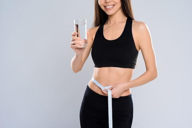 Garota mede a cintura e segura um copo de água.