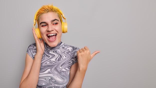 Garota meloman com cabelo tingido de amarelo maquiagem brilhante aponta o polegar para longe mostra um espaço em branco ouve música por meio de fones de ouvido sem fio em cinza