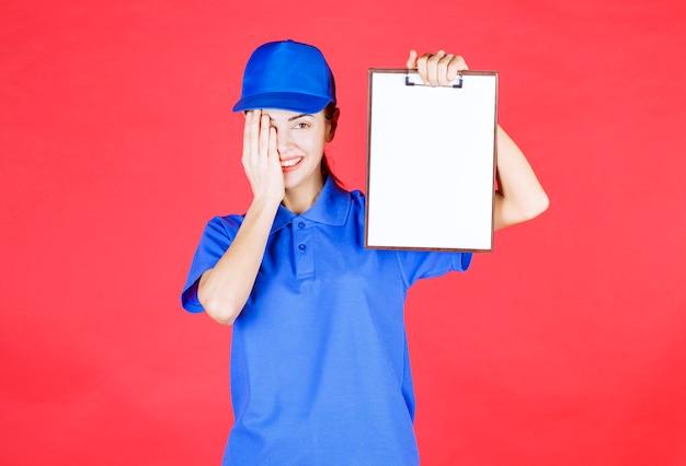 Garota mensageira em uniforme azul segurando uma lista de tarefas e parece pensativa e confusa.