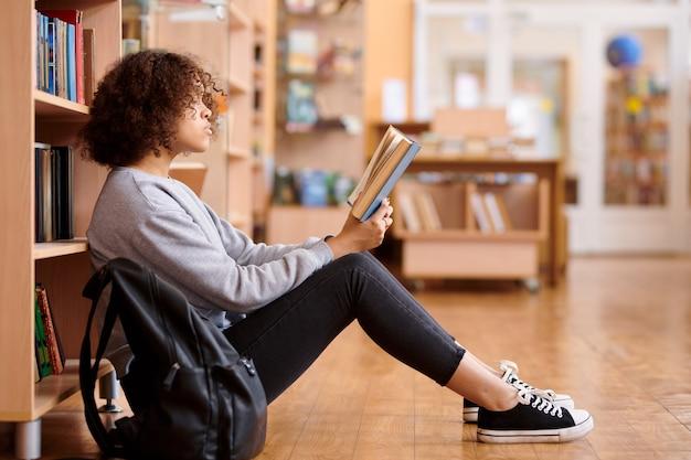 Garota mestiça em trajes casuais sentada no chão perto de estantes na biblioteca da faculdade e lendo um livro