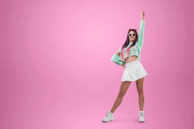Garota milenar com penteado de tranças rosa em roupas turquesa e óculos escuros posando em um fundo rosa. conceito de estilo moderno, inclusividade, individualidade, geração z, cópia espaço.