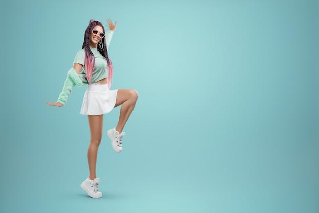 Garota milenar com penteado de tranças rosa em roupas turquesa e óculos escuros posando sobre um fundo azul. conceito de estilo moderno, inclusividade, individualidade, geração z, cópia espaço.