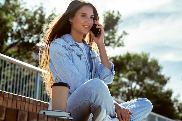 Garota milenar em roupas jeans se senta no banco do parque, se comunica com amigos, colegas, pais no telefone.