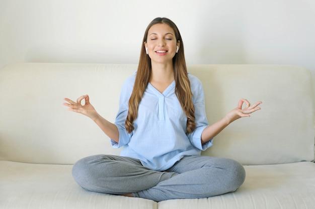 Garota milenar pacífica fazendo exercícios de ioga sozinha.