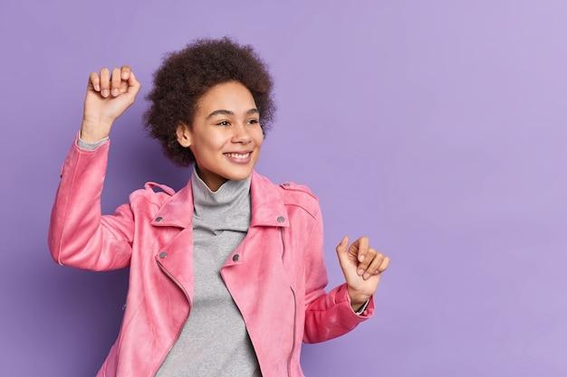 Garota milenar positiva com cabelo encaracolado levanta os braços e dança despreocupada com humor otimista e brinca vestida com jaqueta rosa