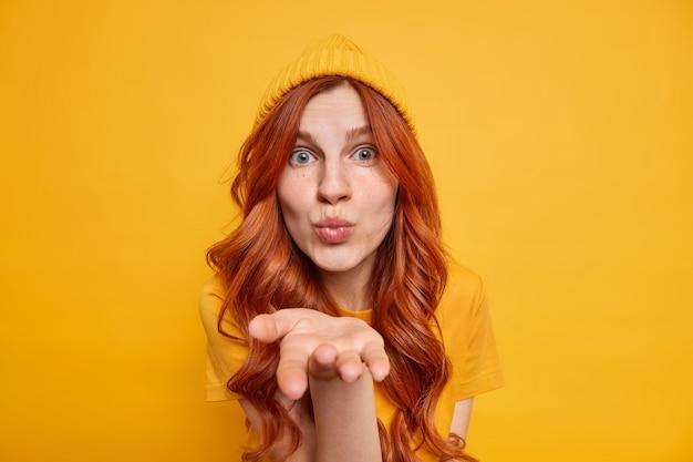 Garota milenar ruiva romântica fofa mantém os lábios dobrados, palma da mão perto da boca, manda beijo no ar, sopra mwah, usa chapéu