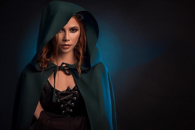 Garota mística posando em fundo escuro, vestindo capa verde, espartilho preto.