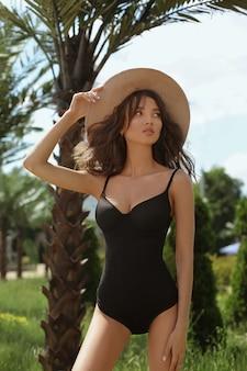 Garota modelo com corpo perfeito sexy, seios grandes e cintura fina, em um maiô preto e chapéu de palha, olhando de lado e posando ao ar livre nos trópicos