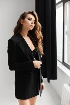 Garota modelo morena sexy blazer de grandes dimensões preto posando no interior branco. moda e beleza