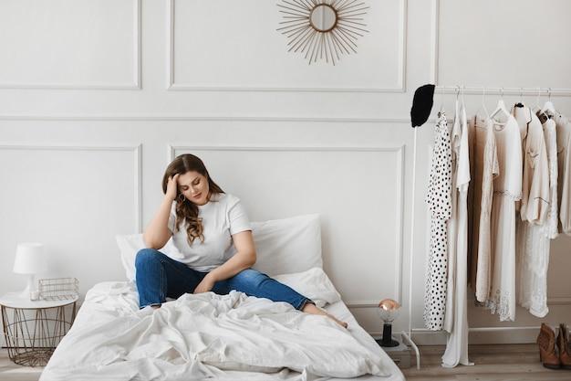 Garota modelo plus-size de jeans e camiseta branca, sentada na cama perto do cabide com roupas e não sabe o que vestir. jovem gorda pensativa não pode escolher roupa. beleza unideal. moda xxl
