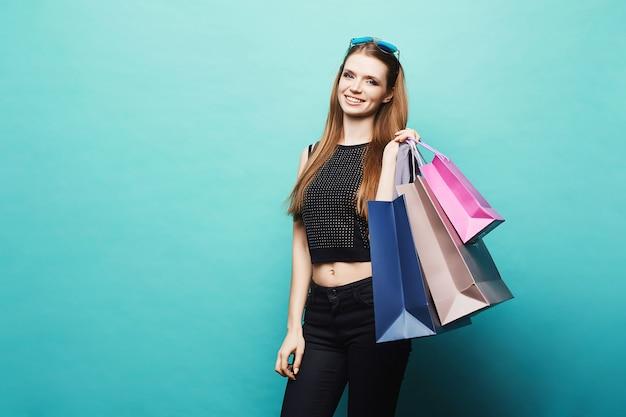 Garota modelo sexy e elegante com corpo perfeito, com maquiagem brilhante e óculos de sol na cabeça, em elegante camiseta preta, em jeans preto posando com sacolas coloridas em turquesa