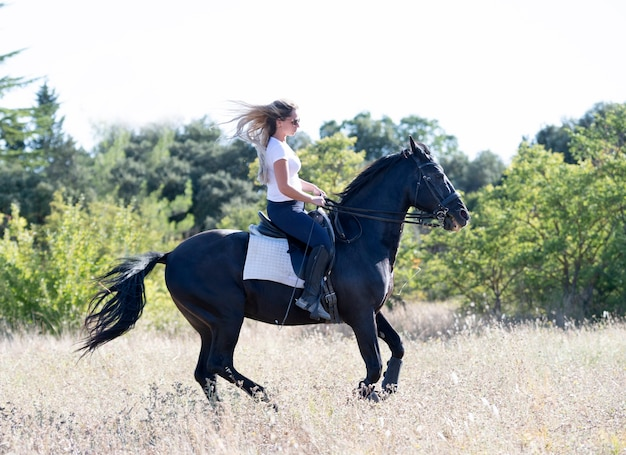 Garota montando está treinando seu cavalo preto