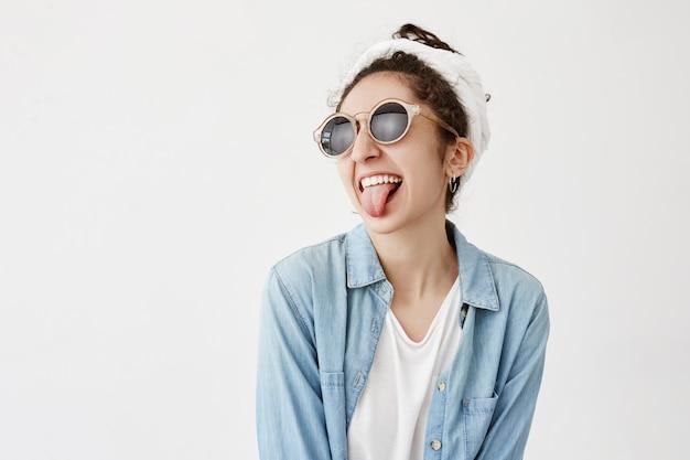 Garota morena de cabelos escuros, usa óculos de sol redondos e camisa jeans, tem estilo próprio, enfia a língua, faz uma careta, diverte-se. emoções e conceito de expressão do rosto