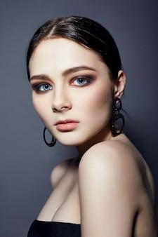 Garota morena fashion sexy tem joias de cabelo preto em volta do pescoço e nas orelhas, grandes olhos azuis