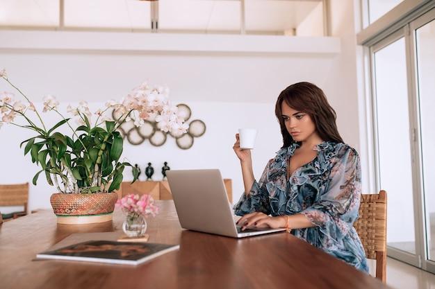 Garota morena jovem sexy tem uma aparência europeia, longos cabelos escuros, pele lisa abriu um trabalho de laptop e pronto para beber café.