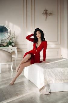 Garota morena sexy em blazer vermelho sedutor posando na cama.