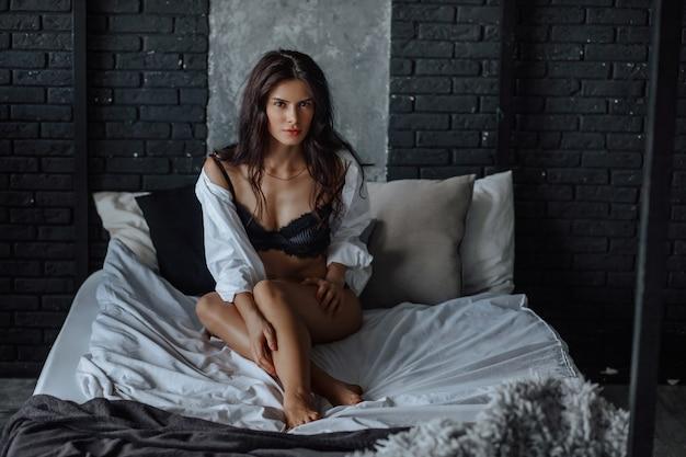 Garota morena sexy na cama de lingerie em fundo escuro