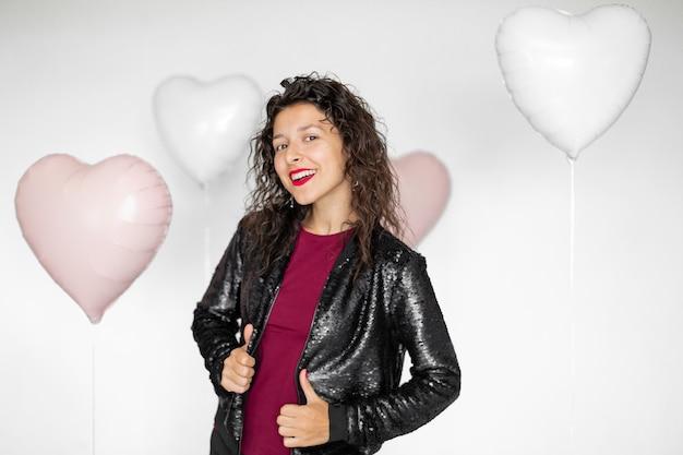 Garota morena sexy posando com balões em forma de coração em um fundo branco.