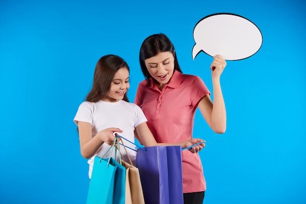 Garota mostra a mãe o que ela comprou na loja.